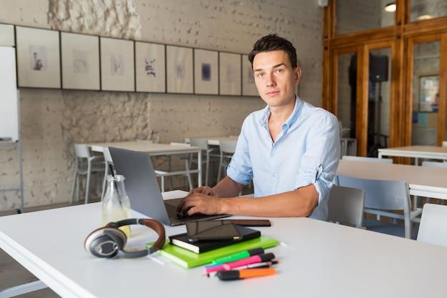 Giovane uomo fiducioso che lavora al computer portatile, seduto in ufficio di co-working