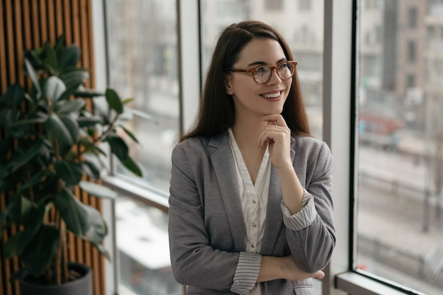 Young confident manager standing in office near window, smiling