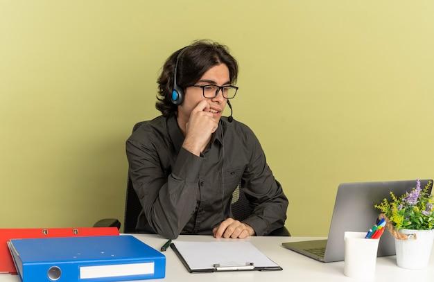 광학 안경에 헤드폰에 젊은 자신감 회사원 남자 사무실 도구를 사용 하 고 노트북을 찾고 책상에 앉아 복사 공간이 녹색 배경에 고립 된 턱에 손을 둔다