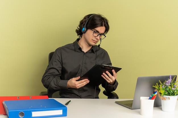 광학 안경에 헤드폰에 젊은 자신감 회사원 남자 노트북을 사용하는 사무실 도구와 책상에 앉아 보유하고 복사 공간이 녹색 배경에 고립 된 클립 보드에서 보이는