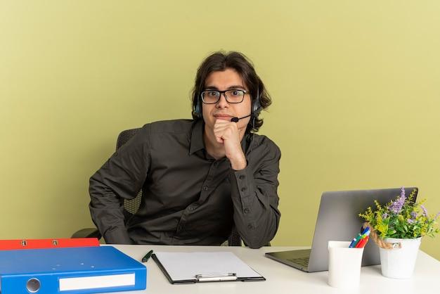 광학 안경에 헤드폰에 젊은 자신감 회사원 남자는 노트북을 사용하는 사무실 도구와 책상에 앉아 복사 공간이 녹색 배경에 고립 된 카메라를보고 턱에 손을 넣습니다