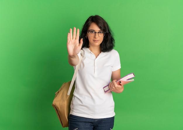 Giovane studentessa abbastanza fiduciosa caucasica con gli occhiali e gesti della borsa posteriore fermare il segno della mano che tiene i libri sul verde con lo spazio della copia