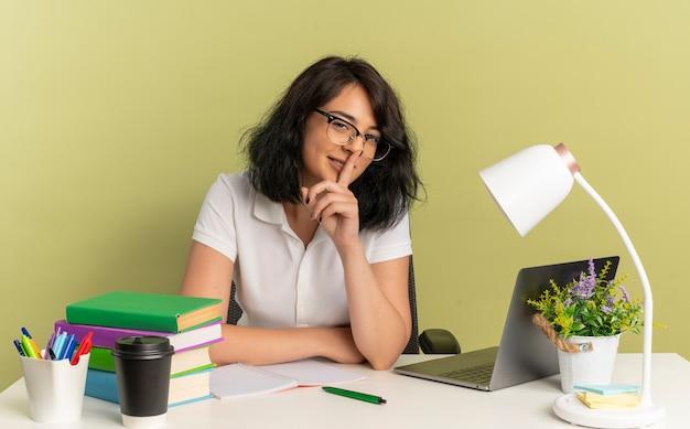안경을 쓰고 젊은 자신감이 예쁜 백인 여학생은 학교 도구 제스처와 함께 책상에 앉아 조용히 복사 공간이있는 녹색 공간에 고립 된 입에 손가락을 넣습니다.