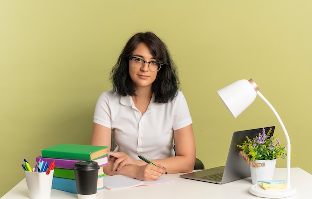 안경을 쓰고 젊은 자신감 꽤 백인 여학생 학교 도구와 책상에 앉아 펜 복사 공간이 녹색 공간에 고립 된 보유