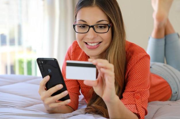 Молодая уверенная в себе симпатичная женщина, лежащая на кровати, читает и вводит номер кредитной карты для покупок в интернете прямо на смартфоне из дома
