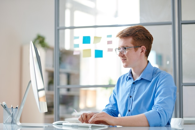 Young confident programmer looking at computer monitor while working by desk in office