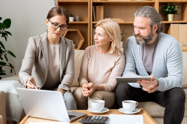 Young confident real estate agent making presentation of new housing project to mature couple at meeting