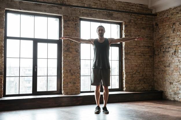 Молодой уверенно спортсмен разминается в тренажерном зале