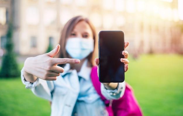 医療マスクの若い自信を持って学生の女性は、空白のスマートフォンの画面を指して、大学のキャンパスに立っています