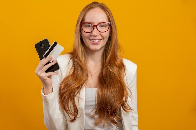Молодая, уверенная, успешная и красивая деловая рыжая женщина, покупающая со смартфона на желтом. профессия, карьера, концепция работы.