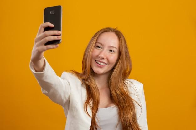 Молодая, уверенная, успешная и красивая деловая рыжая женщина, делающая селфи со смартфоном на желтом. профессия, карьера, концепция работы.