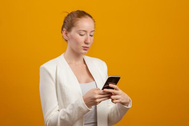 Молодой, уверенный в себе, успешный и красивый бизнес рыжий женщина с смартфона на желтом. профессия, карьера, концепция работы.