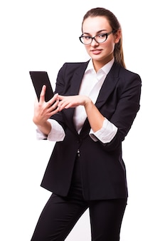 白い壁に隔離されたタブレットコンピューターを持つ若く、自信を持って、成功し、美しいビジネス女性