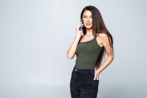 Молодая, уверенная, успешная и красивая женщина с мобильным телефоном на белом