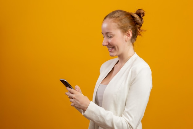 Young, confident, successful and beautiful business redhead woman with the smartphone on yellow. occupation, career, job concept.