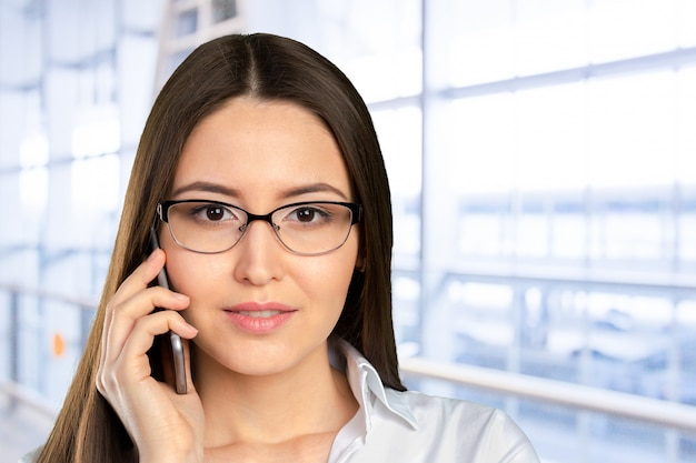 Young, confident, successful and beautiful business woman with the mobile phone isolated