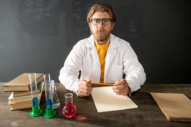 Молодой уверенный в себе учитель химии в белом халате, глядя на свою онлайн-аудиторию, сидя за столом на пустой доске