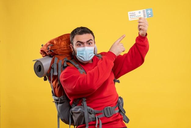 Giovane viaggiatore fiducioso che indossa una maschera medica con zaino e tiene il biglietto su giallo