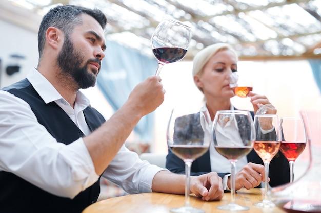 Молодой уверенный в себе эксперт винодельни с одним из бокалов дегустирует новый сорт красного вина с коллегой поблизости