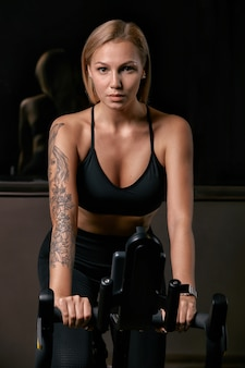 Young confident woman athlete exercising on bicycle indoors. attractive determined fitness girl doing cycling exercises in dark gym. functional workout training of sports girl. cardio training