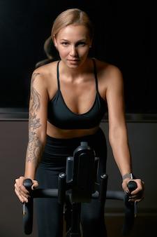 Молодой спортсмен уверенно женщина работая на велосипеде в помещении. привлекательная решительная фитнес-девушка делает упражнения на велосипеде в темном тренажерном зале. функциональная тренировка спортивной девушки. кардио тренировки.