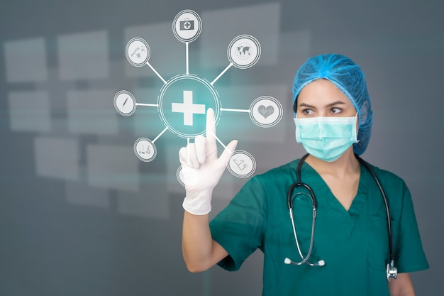 Young confident woman doctor in green scrubs is wearing surgical mask over grey studio