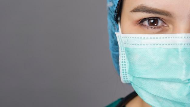 Молодая уверенная женщина-врач в зеленом халате носит хирургическую маску над серым