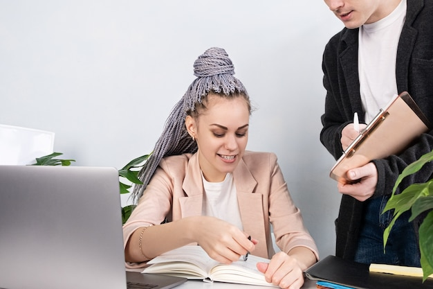 若い自信のある女性リーダーがアシスタントに何かを説明し、ワークテーブルとラップトップのジャケットを着てオフィスに座っているときにノートを指さします。女性労働者、女性の力と独立