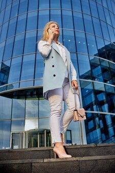젊은 자신감 있는 여성은 비즈니스 센터 근처에 서서 스마트폰으로 이야기합니다.