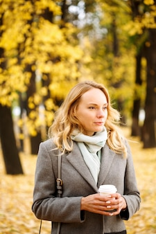 Young confident woman with coffee outdoors in sunny autumn day closeup portrait
