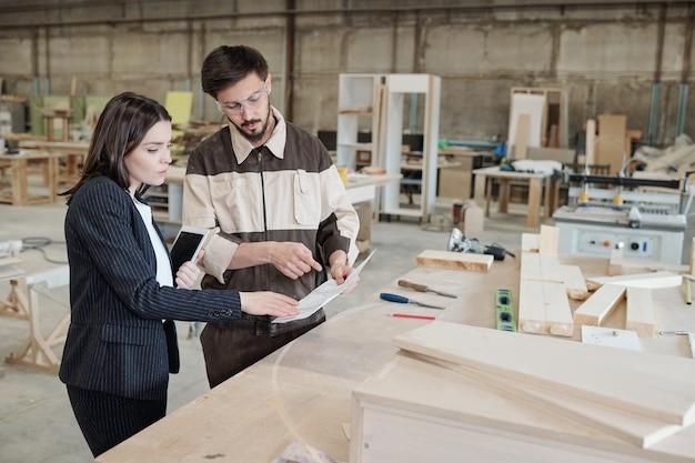 Молодой уверенный в себе работник в форме и защитных очках, указывая на эскиз нового предмета мебели и объясняя его коллеге