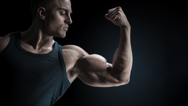 검은 배경에 서 있고 팔 뚝 근육 포즈를 취하는 젊은 자신감 근육 질의 보디 남자 검은 배경에 스튜디오에서 클래식 보디 빌딩 샷