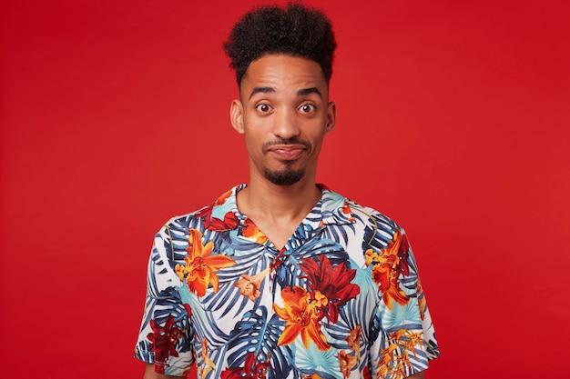若い混乱したアフリカ系アメリカ人の男がアロハシャツを着て、不思議と誤解でカメラを見て、腕を組んで赤い背景の上に立っています。