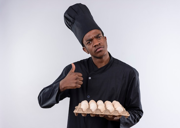 Young confused afro-american cook in chef uniform holds batch of eggs and thumbs up isolated on white wall