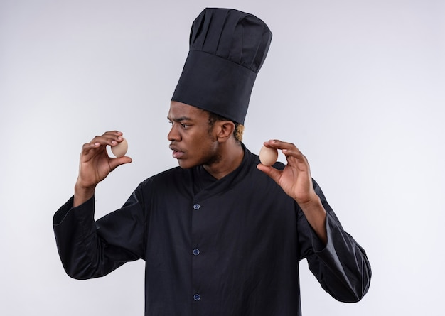 Young confused afro-american cook in chef uniform holds eggs on both hands isolated on white wall