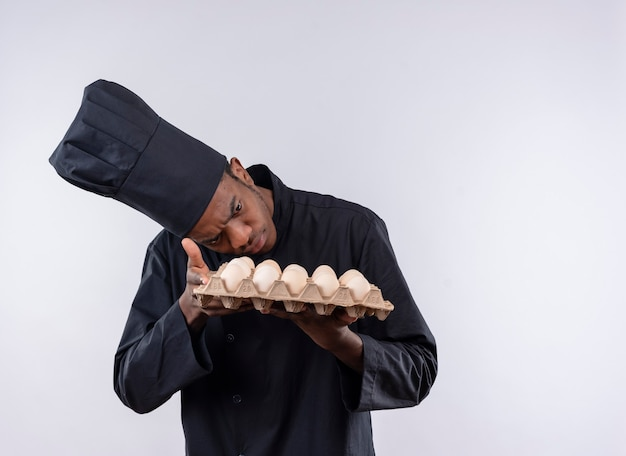 Young confused afro-american cook in chef uniform holds and looks at batch of eggs isolated on white wall