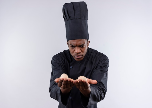 Young confused afro-american cook in chef uniform holds and looks at eggs isolated on white wall