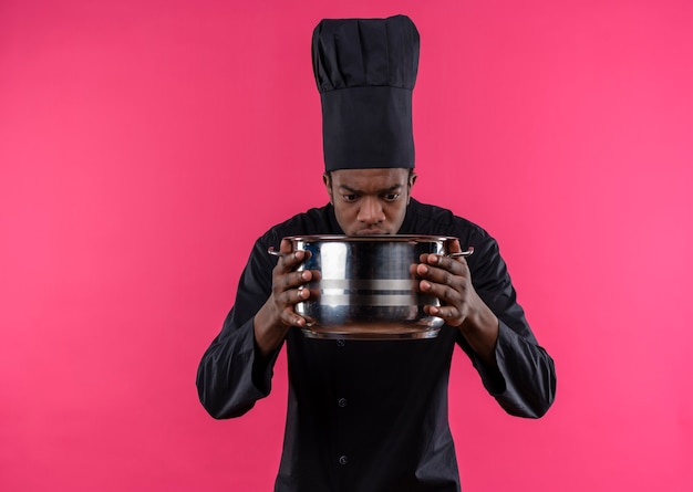 Young confused afro-american cook in chef uniform holds and looks at saucepan isolated on pink wall