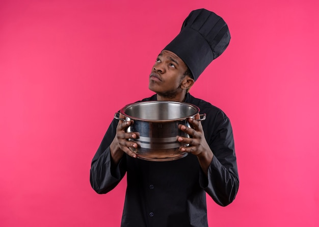 Young confused afro-american cook in chef uniform holds saucepan and looks up isolated on pink wall