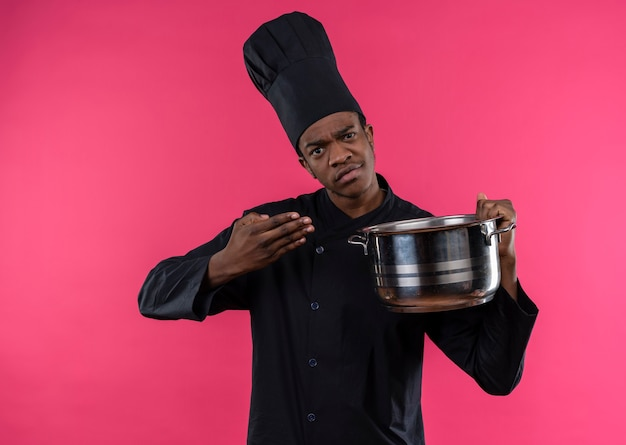 Young confused afro-american cook in chef uniform holds saucepan and points with hand isolated on pink wall