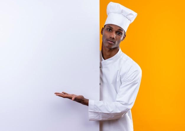 Il giovane cuoco afroamericano confuso in uniforme del cuoco unico sta dietro la parete bianca e indica alla parete con la mano isolata sulla parete arancione
