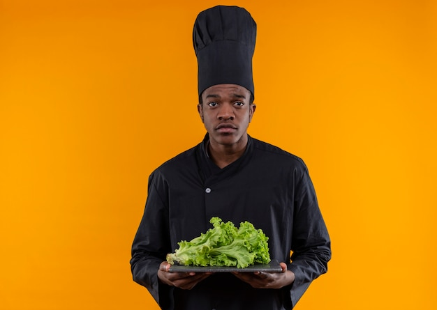 シェフの制服を着た若い混乱したアフリカ系アメリカ人の料理人は、オレンジ色の壁に分離されたまな板にサラダを保持します