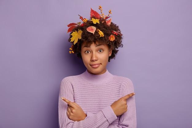 La giovane donna afro confusa indica lateralmente, sceglie tra due opzioni, chiede di aiutare a prendere una decisione, indica destra e sinistra, ha foglie autunnali e bacche nei capelli ricci, isolate sul muro viola
