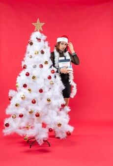 Молодая смущенная красивая женщина в шляпе санта-клауса стоит за украшенной елкой, держит подарки и что-то ищет