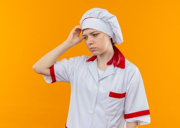 Il giovane chef femmina bionda confuso in uniforme da chef tiene la testa e guarda in basso isolato sulla parete arancione