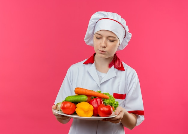 シェフの制服を着た若い混乱した金髪の女性シェフは、ピンクの壁に隔離されたプレート上の野菜を保持し、見ています