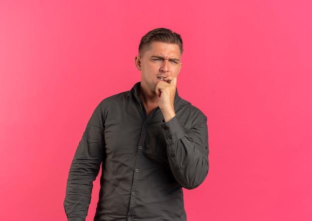Il giovane uomo bello biondo confuso mette la mano sul mento che esamina il lato isolato su fondo rosa con lo spazio della copia