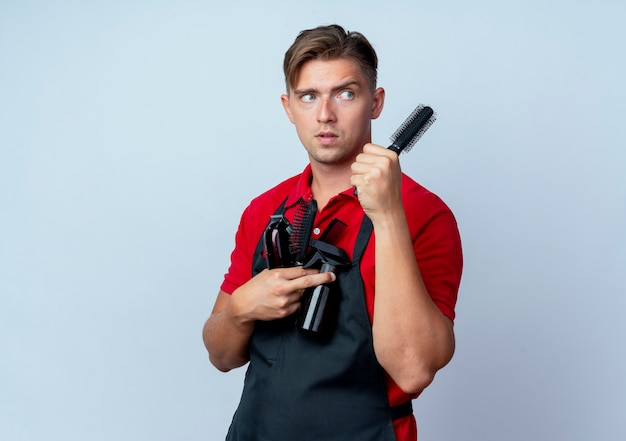 Young confused blonde male barber in uniform holds barber tools looking at side