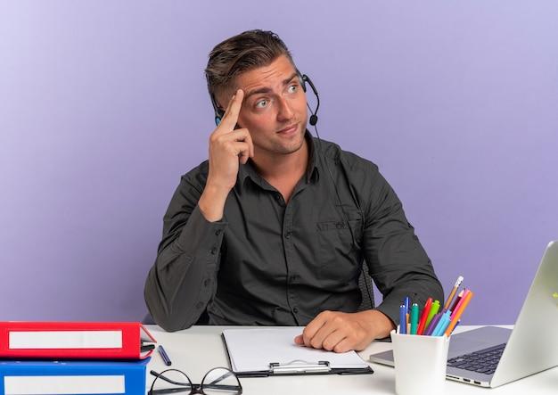 Giovane uomo di lavoratore di ufficio bionda confuso sulle cuffie si siede alla scrivania con strumenti di office utilizzando il computer portatile mette la mano sulla testa guardando il lato isolato sullo spazio viola con lo spazio della copia