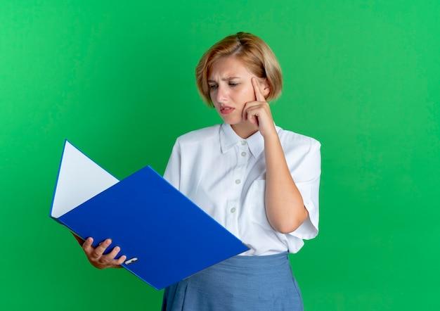 Молодая сбитая с толку русская блондинка держит и смотрит на папку с файлами